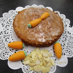 Aargauer Rüeblitorte (Argovian Carrot Cake) with main ingredients on a doilie