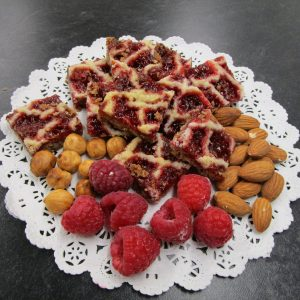 Homemade Linzer Carées (Linzer squares) with main ingredients on a doilie