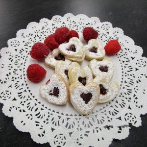 Spitzbuebe (heart-shaped shortbreads with raspberry jam) on a doilie